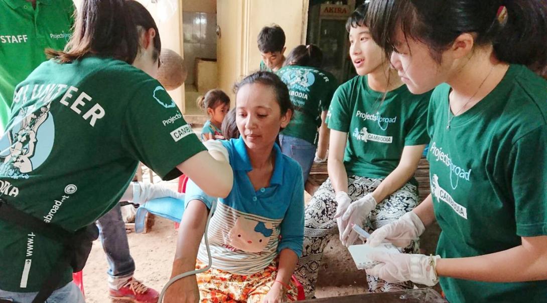 カンボジアの地域内での公衆衛生活動で血圧測定に取り組む高校生ボランティア